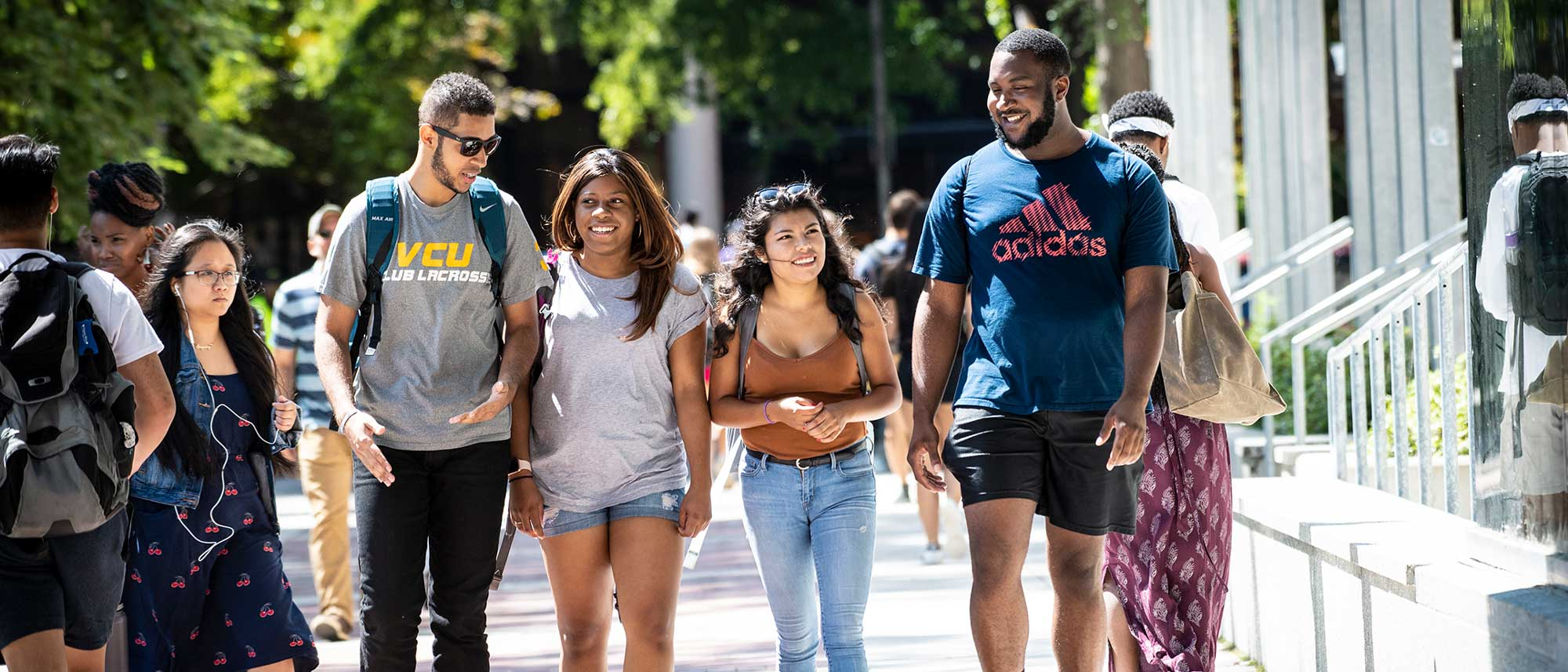 four v.c.u. students walking across campus on a sunny day